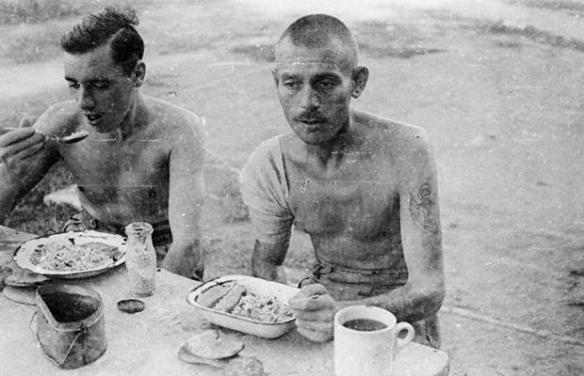 POWs at Changi camp, Singapore, eating their rations of rice and fruit Picture: IMPERIAL WAR MUSEUM