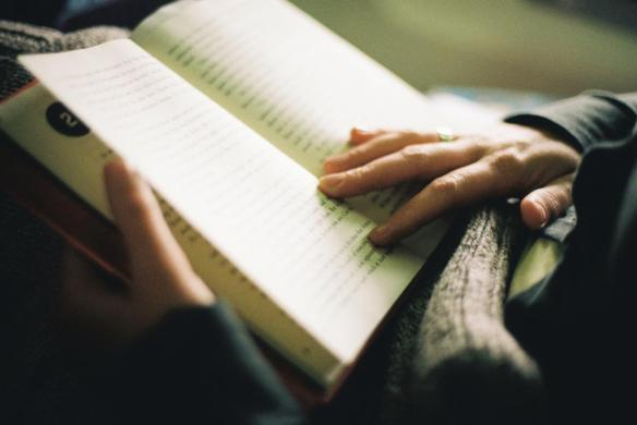 Woman reading a book, indoor light, hands close-up